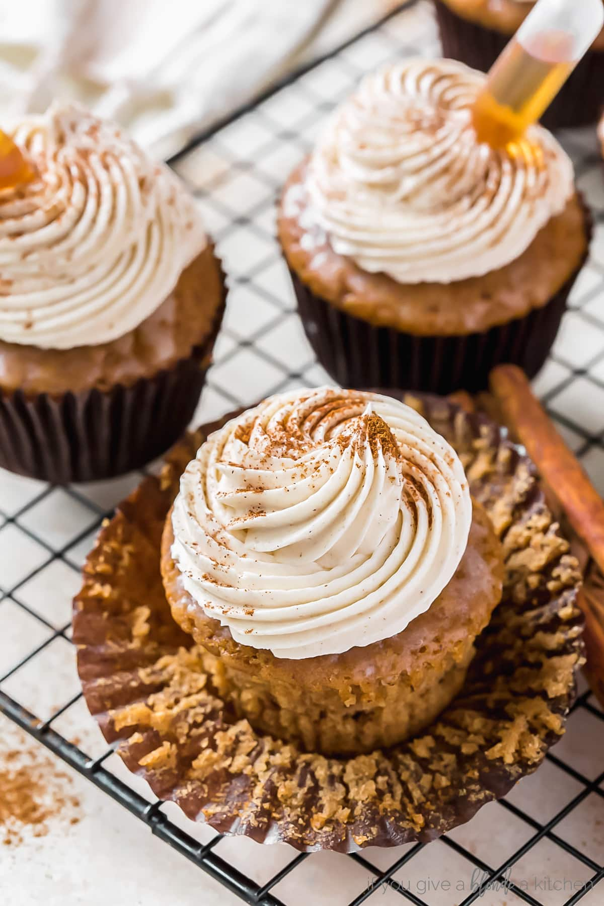 buttered rum cupcakes topped with rum frosting and cinnamon on unwrapped paper cupcake liner