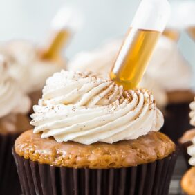 tops of buttered rum cupcakes with frosting and mini injector of rum inserted to cupcakes