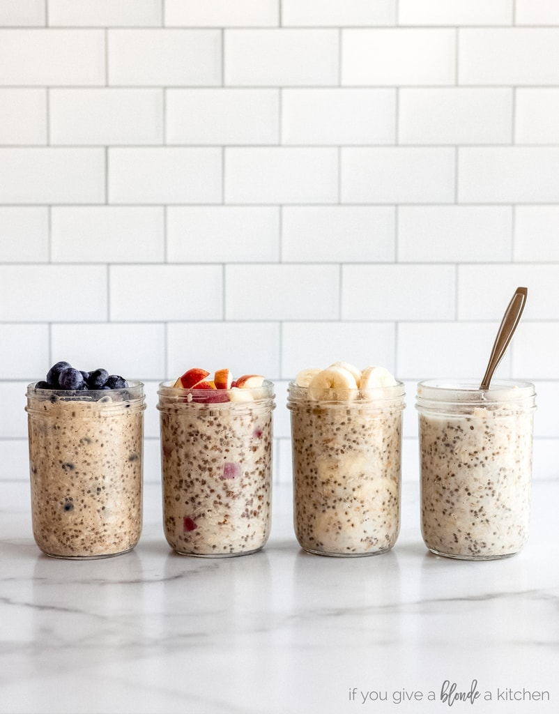 four jars of overnight oats on marble surface