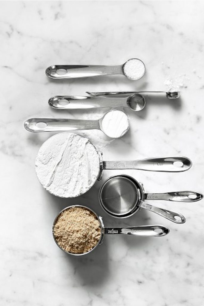 all clad measuring cups and spoons on marble surface