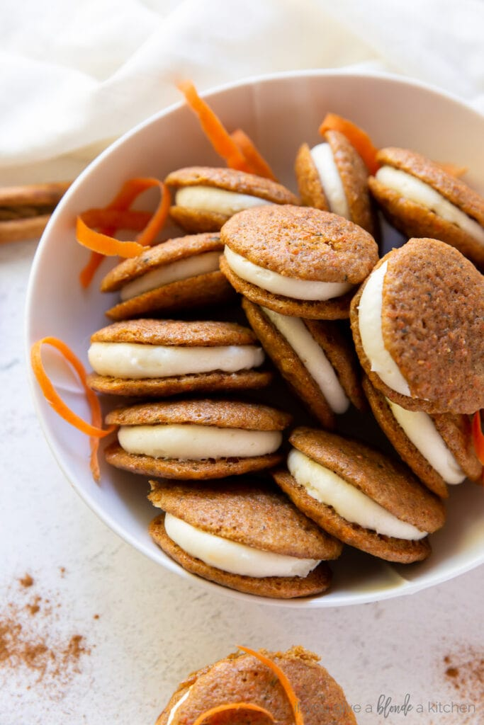 bowl filled with carrot cake whoopie pies and a couple pieces of shredded carrots
