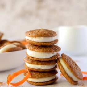 stack of four carrot cake whoopie pies with one whoopie pie leaning against stack