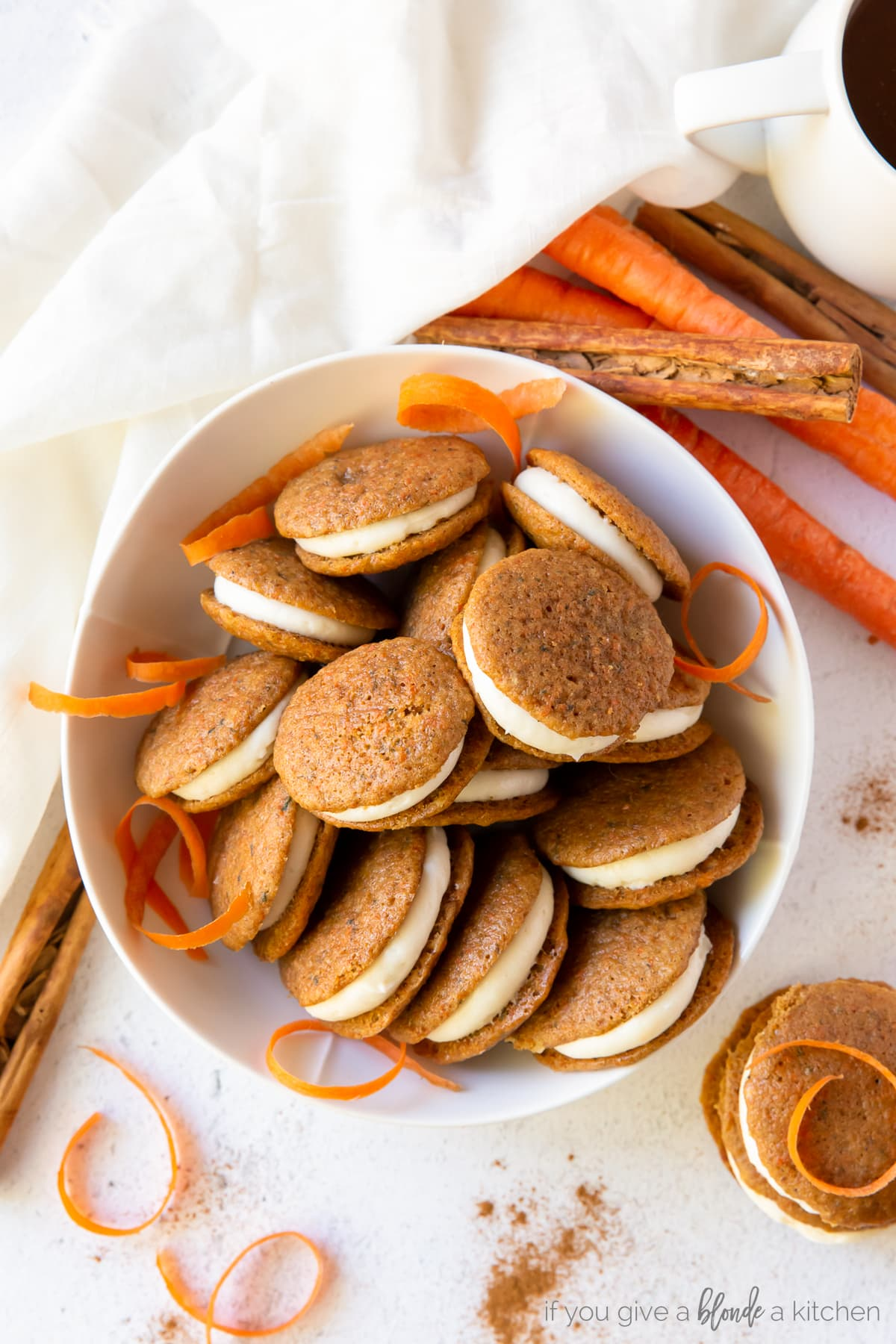 Mini carrot cake whoopie pies on a plate with blue striped towel