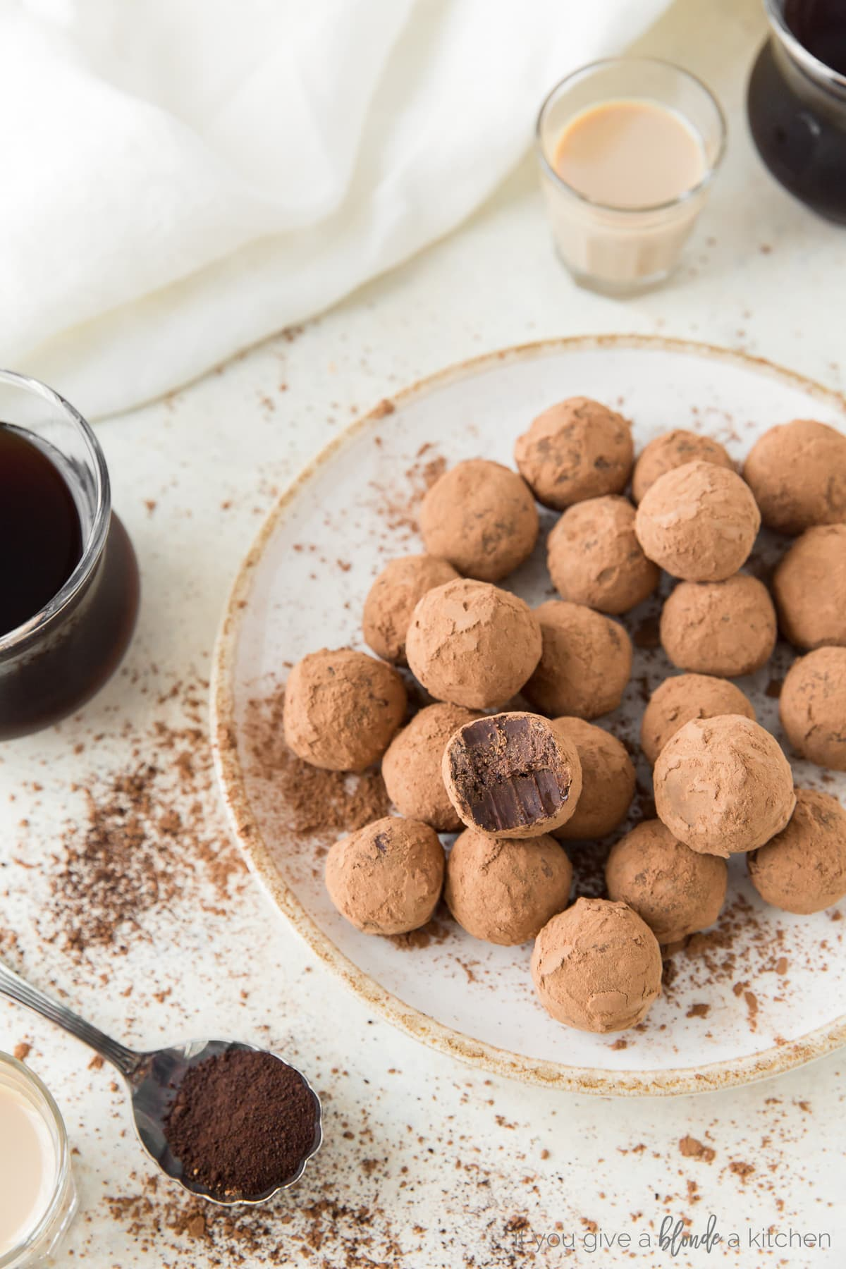 plate of cocoa covered espresso truffles; spoon of espresso and glass of coffee next to plate