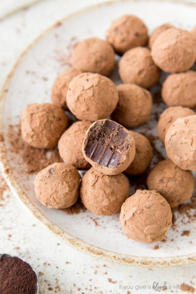 chocolate truffles coated in cocoa powder on plate; top truffle with bite out of it