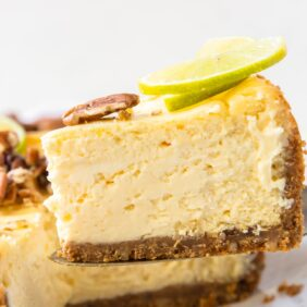 thick slice of lime curd cheesecake on cake knife lifted up