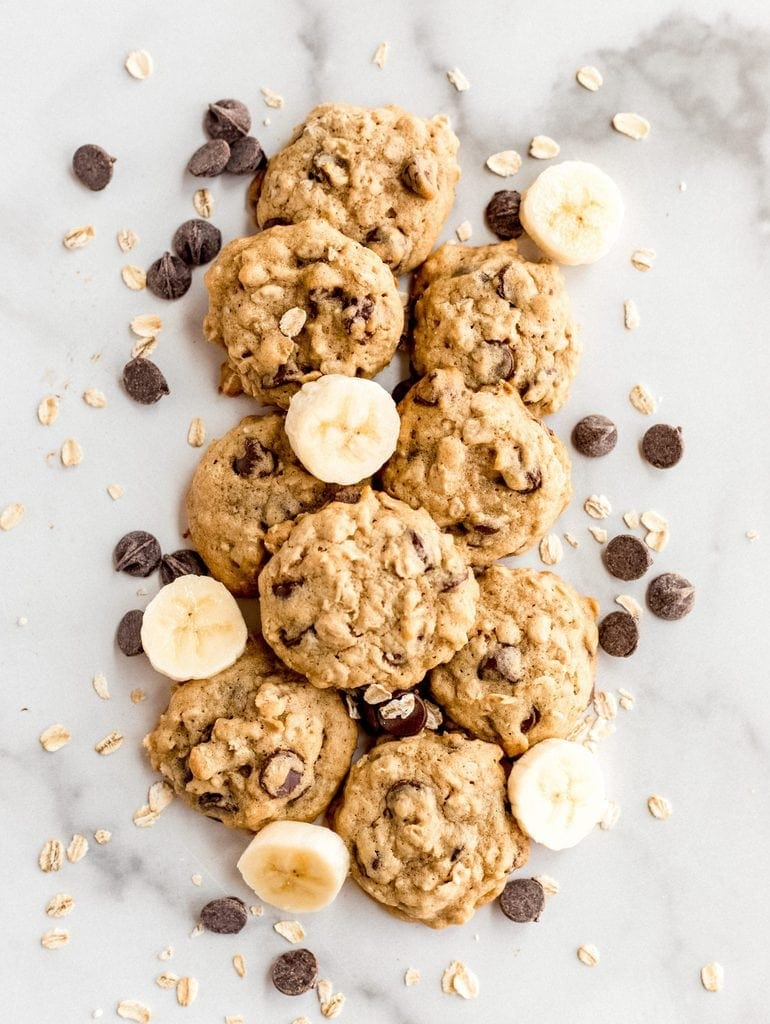 banana oatmeal cookies on marble with slices of banana, chocolate chips and oats