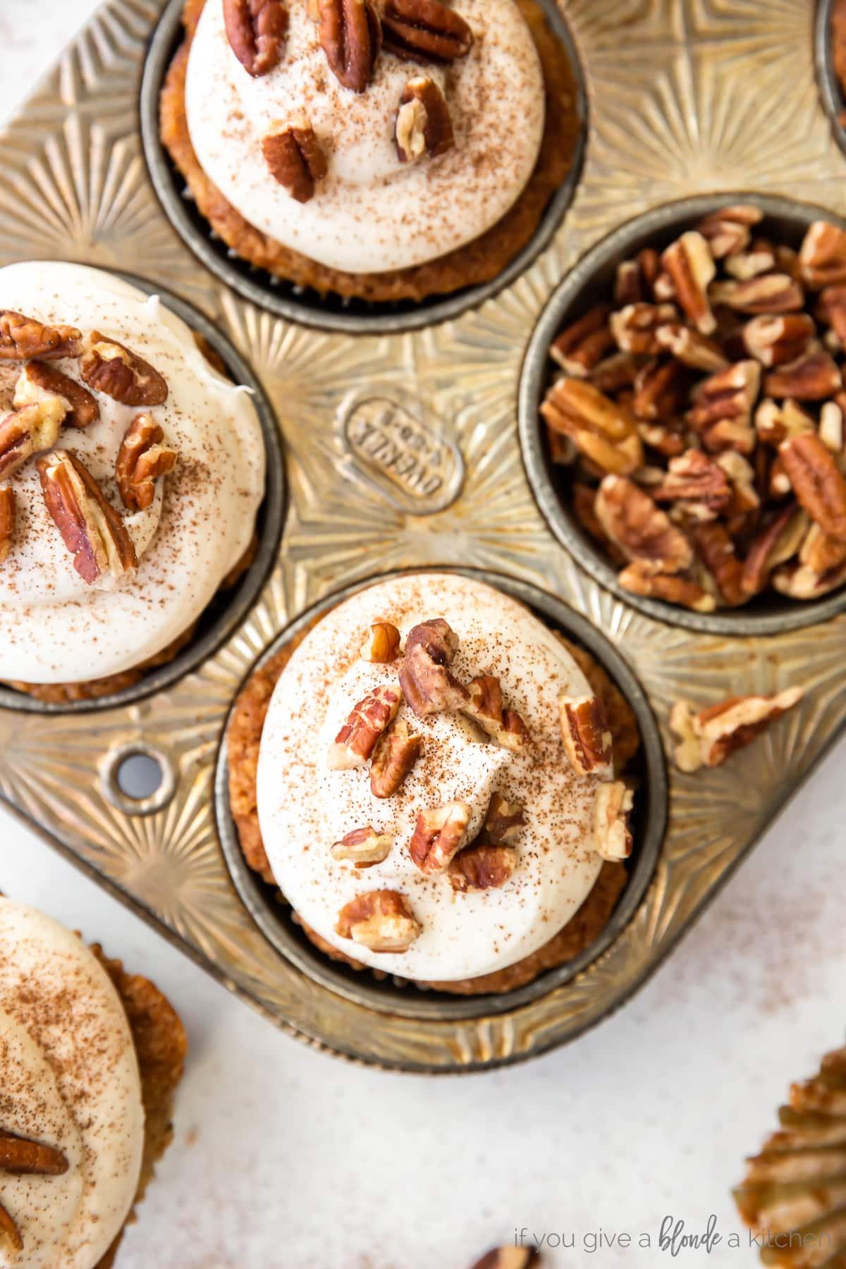 antique muffin tin with hummingbird cupcakes topped with cream cheese frosting and pecans