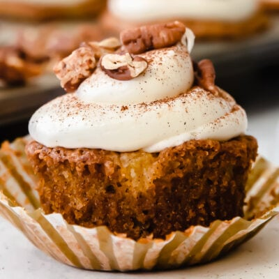 hummingbird cupcake topped with cream cheese frosting and pecans on an open paper liner