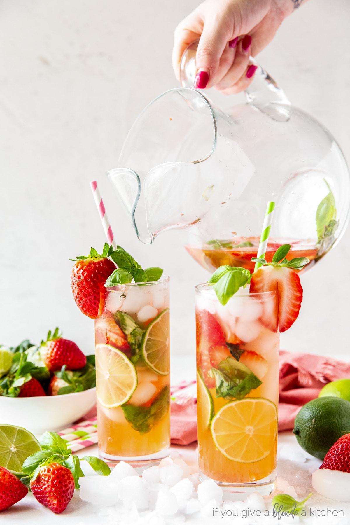 glass pitcher pouring strawberry mojito into two glasses