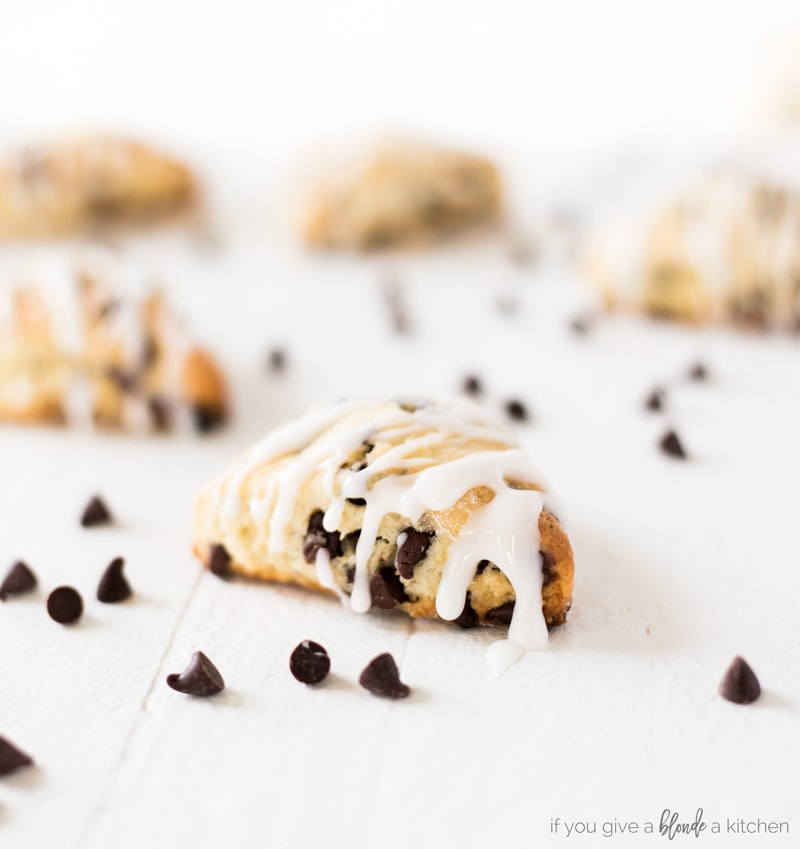 two bite chocolate chip mini scones with icing dripping and mini chocolate chips scattered