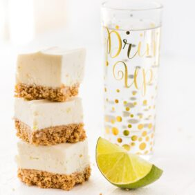 No bake margarita cheesecake bites stack of three with tequila shot glass and lime wedge