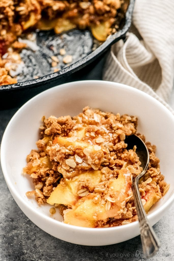 peach crisp serving in bowl with spoon