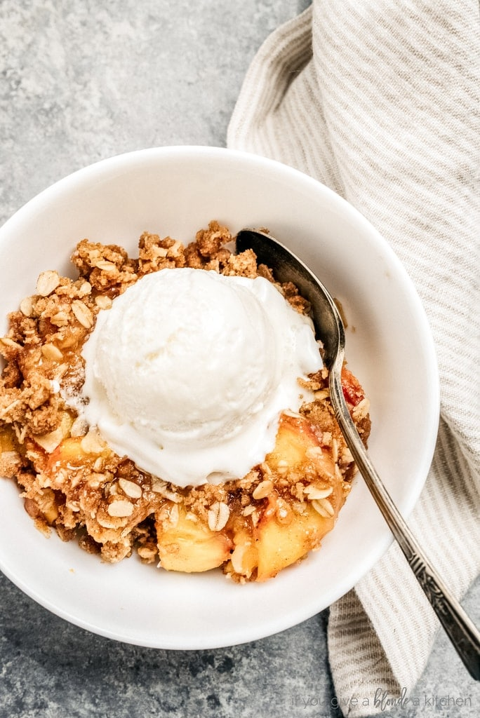 bowl of peach crisp, scoop of vanilla ice cream