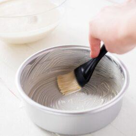 magic cake pan release paste. silver round cake pan with silicone pastry brush. homemade paste brushing inside of pan