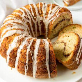 cinnamon zucchini bundt cake with glaze dripping down and two slices cut out