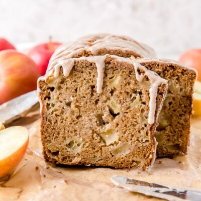 slice of apple cider bread with chunks of apples and glaze dripping down