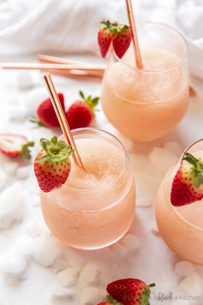 frose in stemless wine glasses with metal straws and strawberries on the rim