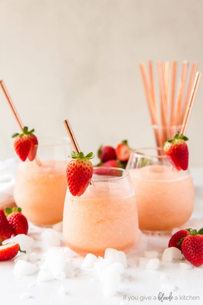 three stemless wine glasses filled with frozen rose and garnished with a strawberry