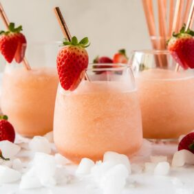 three frozen rose glasses with strawberries and stainless steel rose gold straws