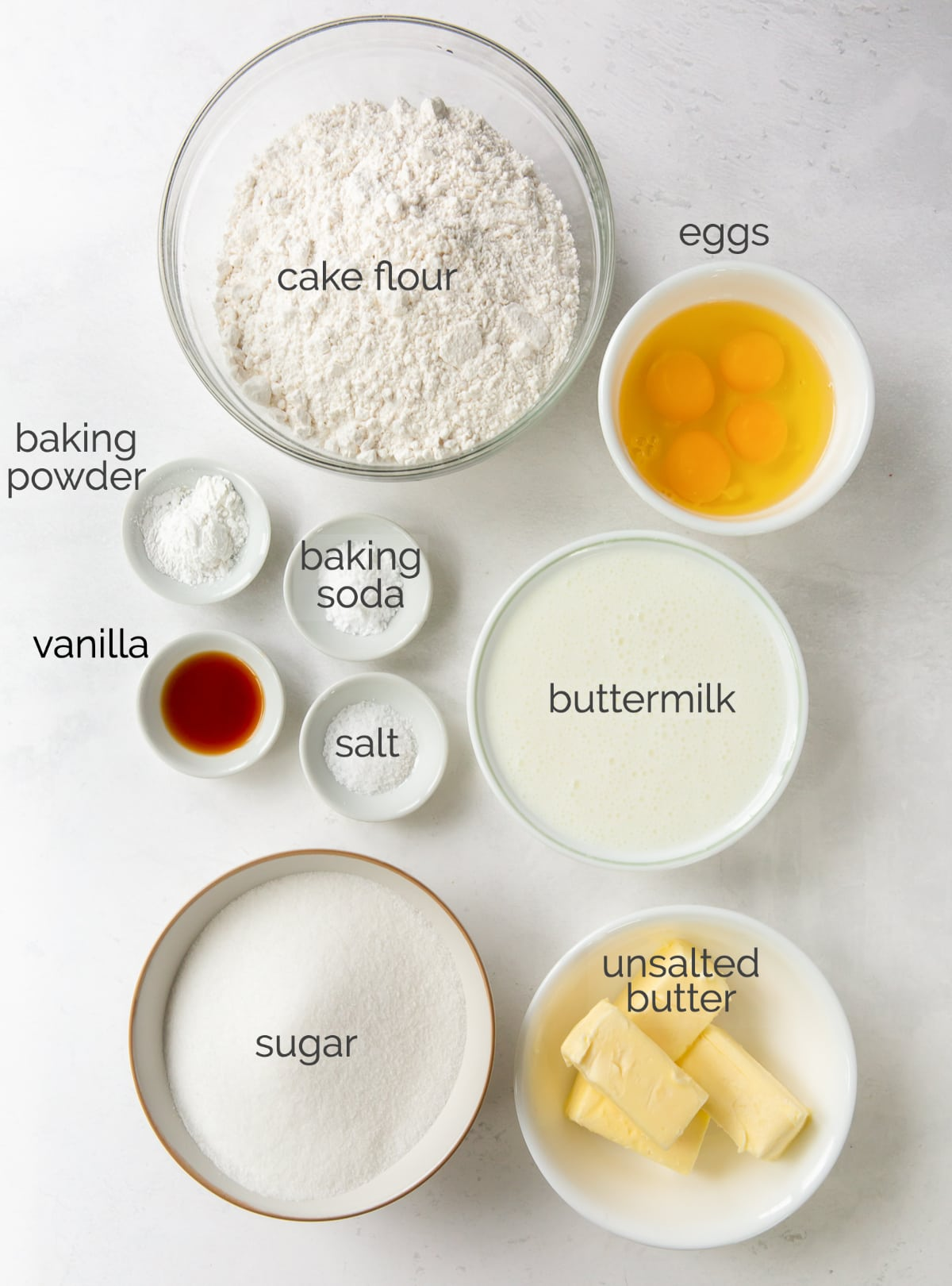 vanilla layer cake ingredients in bowls labeled with text