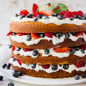 triple berry layer cake with exposed layers and summer berries