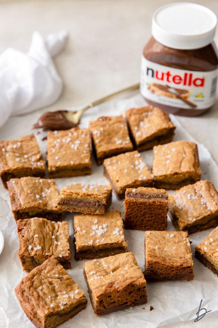 salted nutella blondies on crinkled wax paper and jar of nutella behind bars