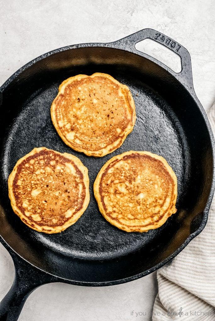 three pumpkin pancakes on a black skillet
