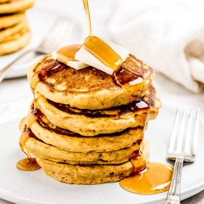 maple syrup poured on stack of pumpkin pancakes