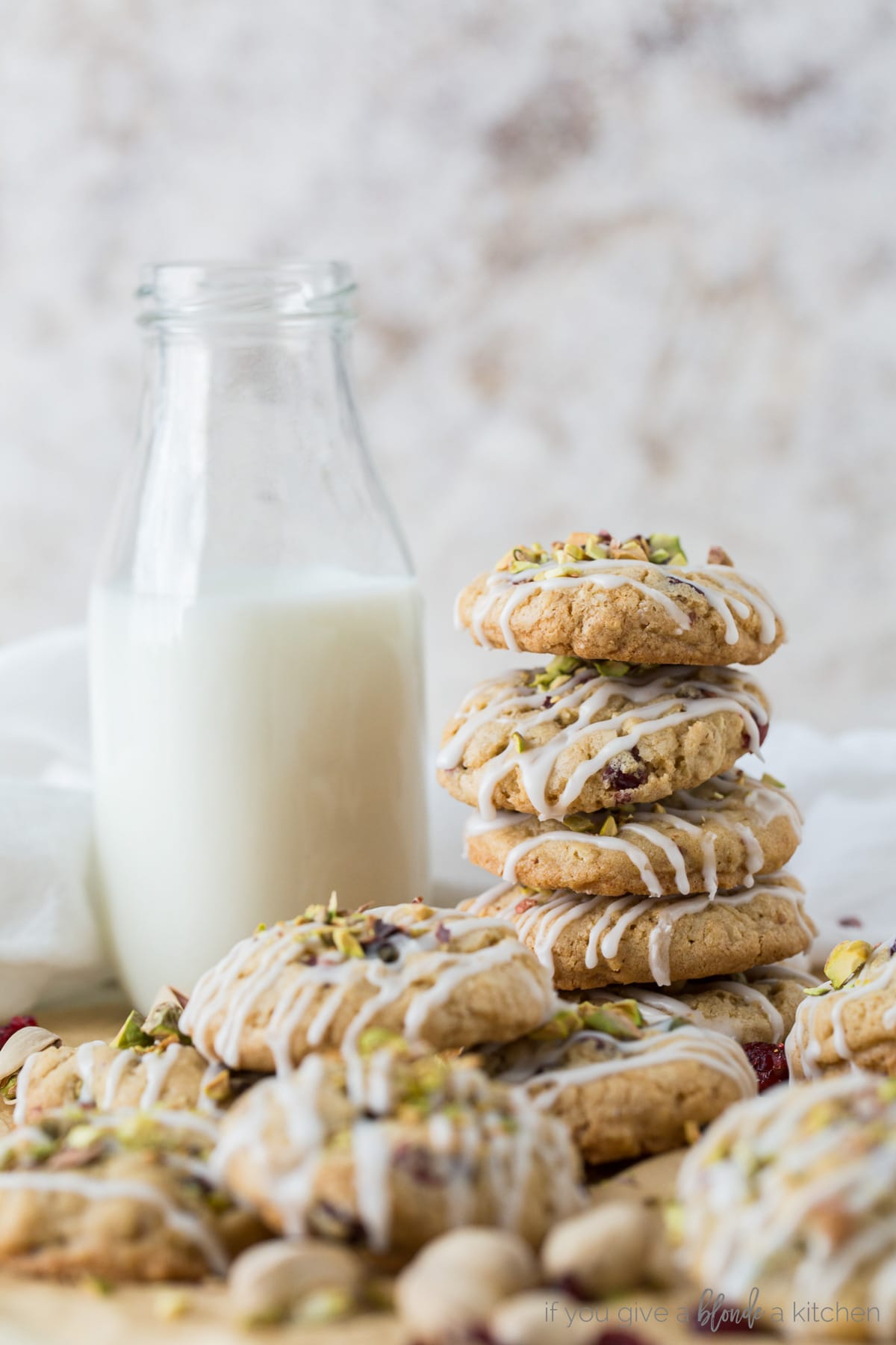 pile of cranberry pistachio oatmeal cookies with icing next to bottle of milk