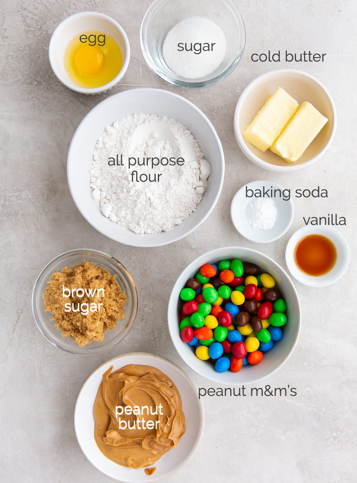 peanut m&m cookie ingredients in bowls labeled with text