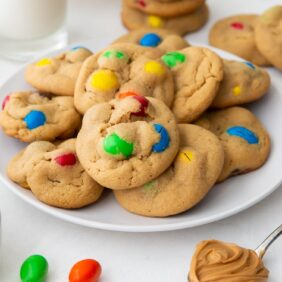 plate of peanut m&m cookies with m&ms and more cookies scattered around plate