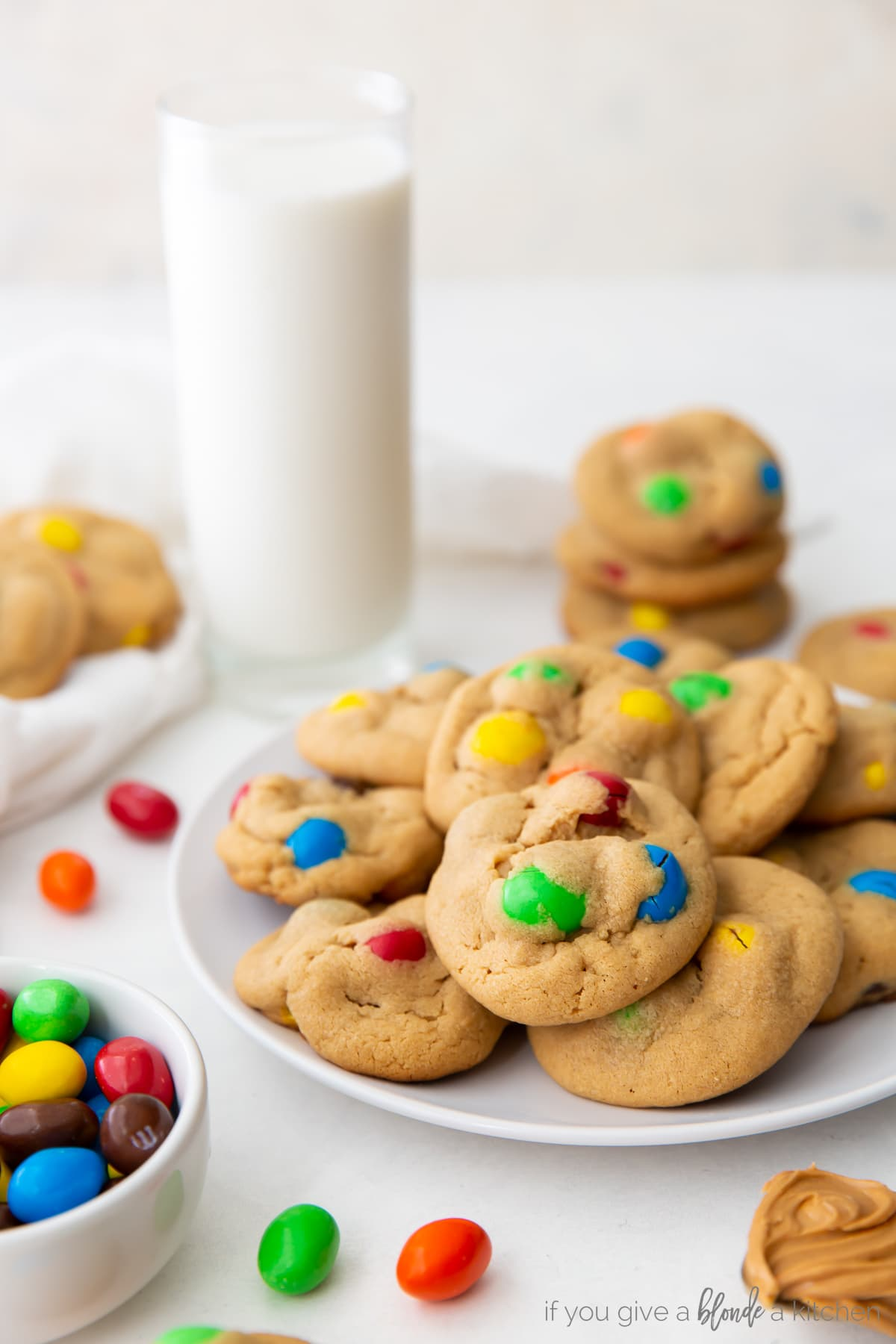peanut M&M cookies on cookie sheet with bowl of colorful m&ms