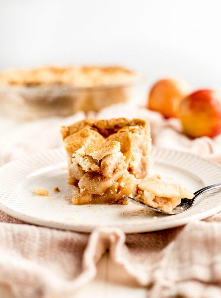 slice of apple pie with fork on plate