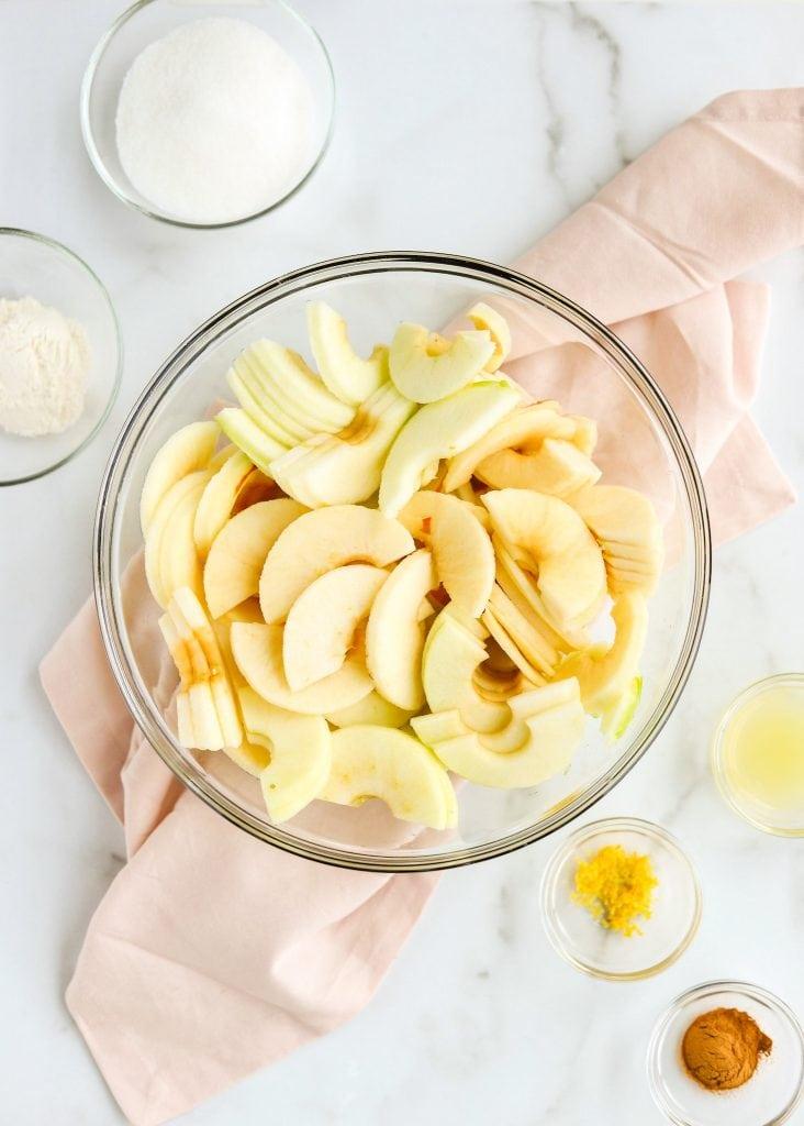 apple pie ingredients in bowls sliced apples cinnamon sugar lemon