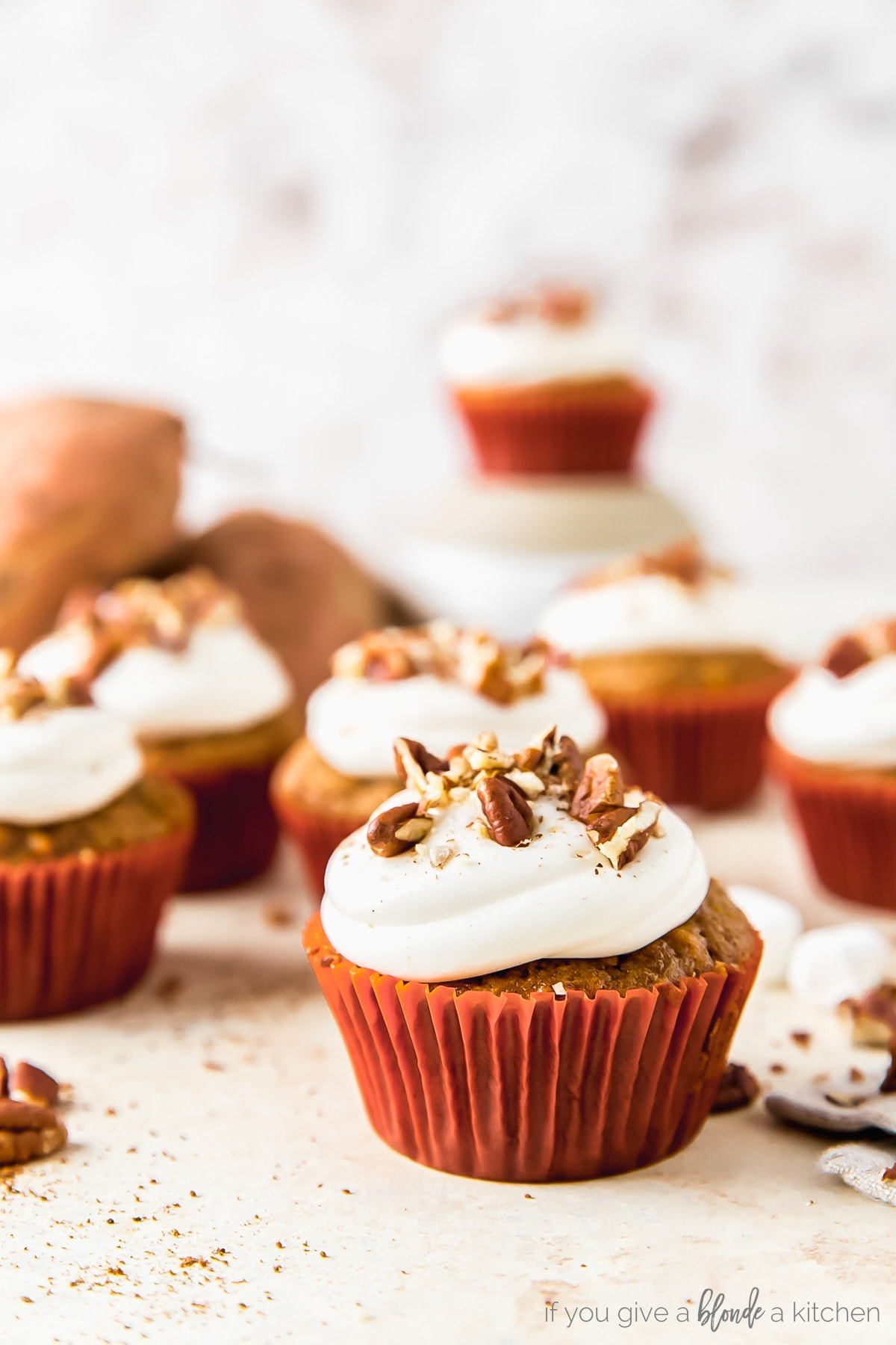 sweet potato cupcake topped with marshmallow frosting and chopped pecans