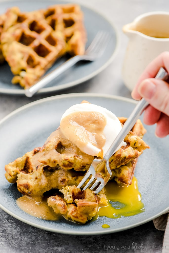 hand holding fork taking bite of leftover stuffing waffles with poached egg and gravy
