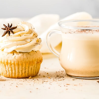eggnog cupcake with frosting next to glass mug of spiked eggnog