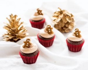 mini gingerbread cupcakes in red cupcake liners with gingerbread man candy on top
