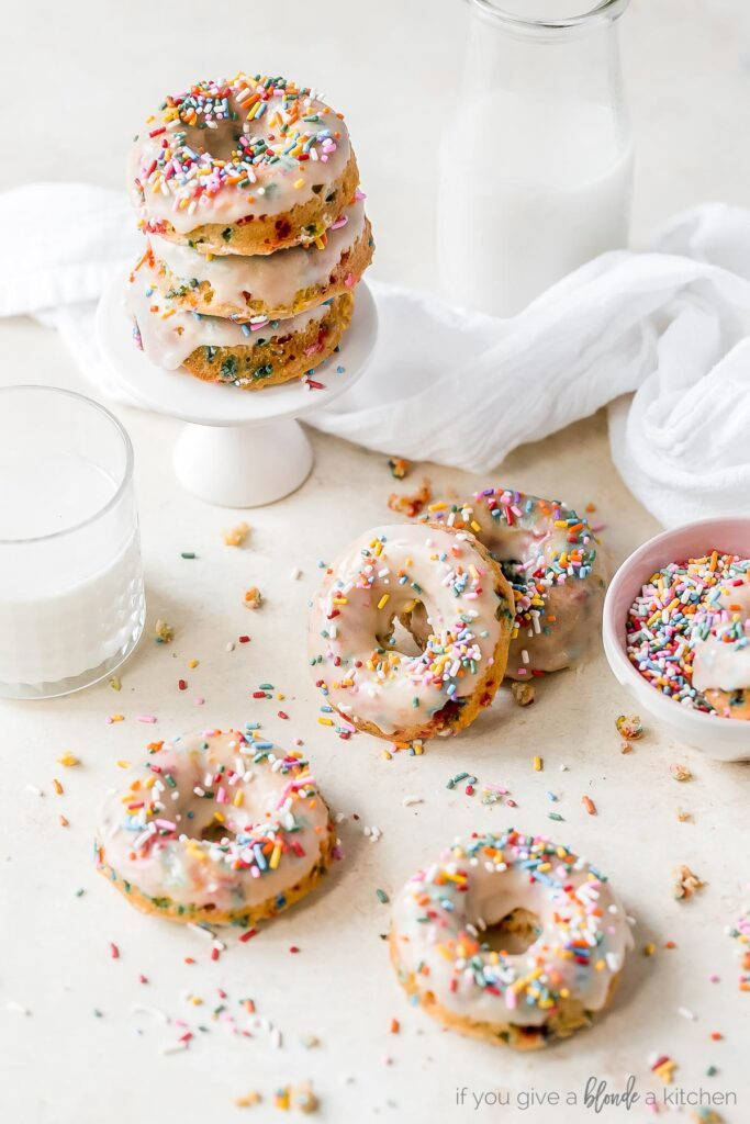 birthday donuts with icing and sprinkles on surface with glass of milk and sprinkles