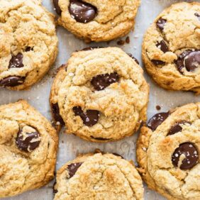 homemade chocolate chip cookies with chocolate chunks and sea salt on parchment paper