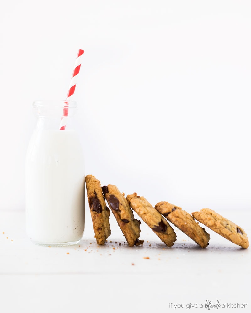 homemade chocolate chip cookies lined up next to each other next to glass of milk