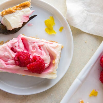 raspberry cheesecake bar with fork taking a bite on round white plate with lemon zest