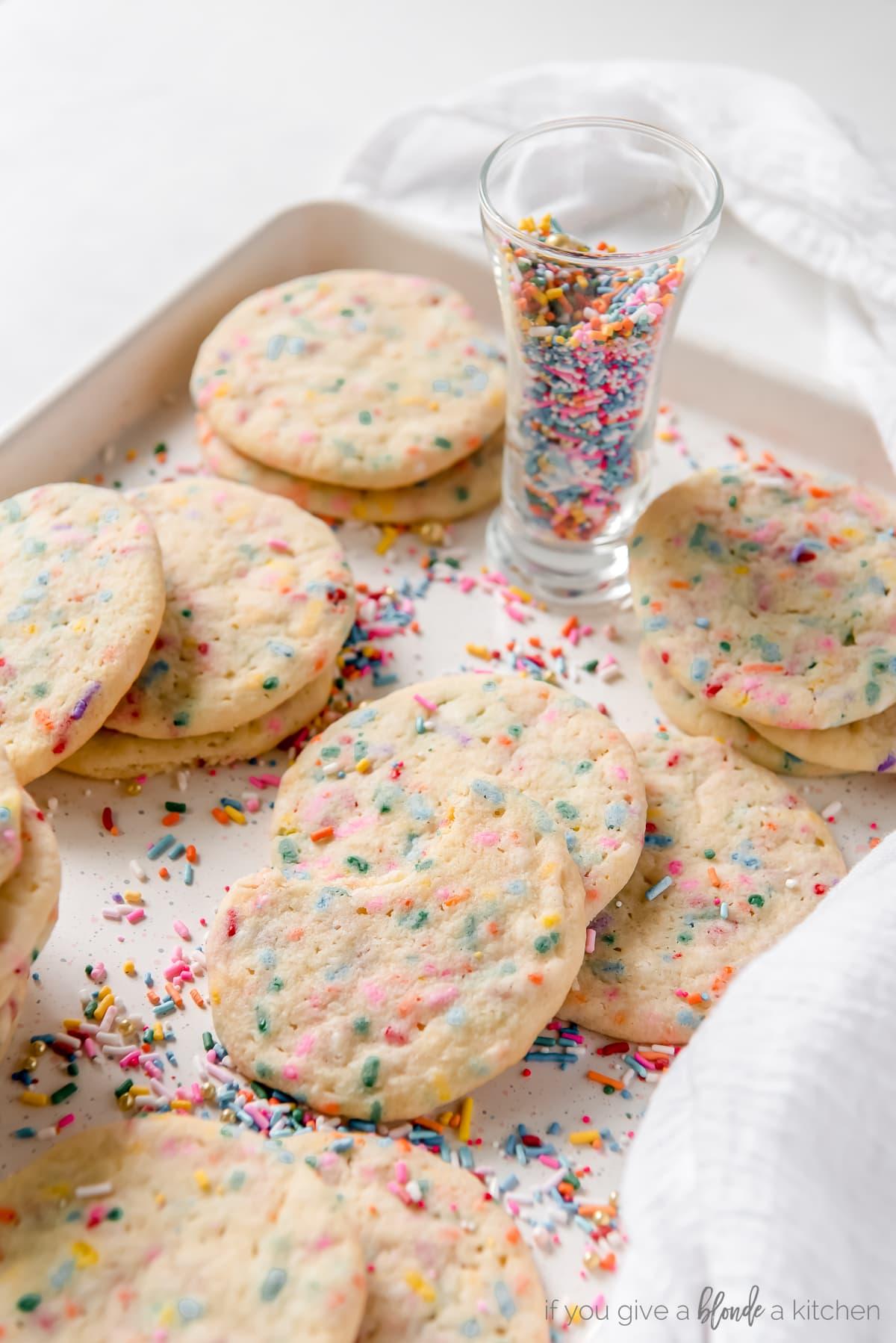 sprinkle sugar cookies piled on baking sheet with shot glass of rainbow sprinkles