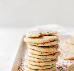 stack of a dozen sprinkle sugar cookies on a baking sheet covered in rainbow sprinkles