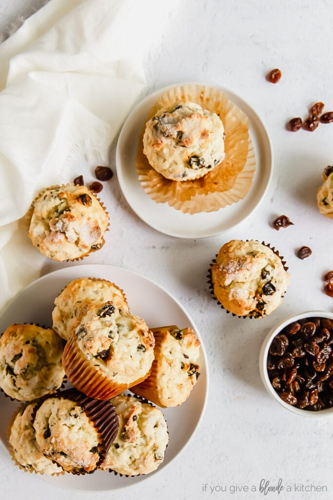 Irish soda bread muffins piled on a plate with one muffin on a smaller plate and bowl of raisins