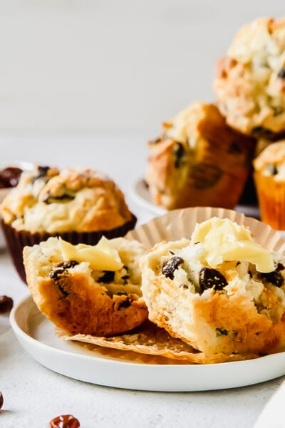 irish soda bread muffin cut in half with butter with more muffins on plate behind