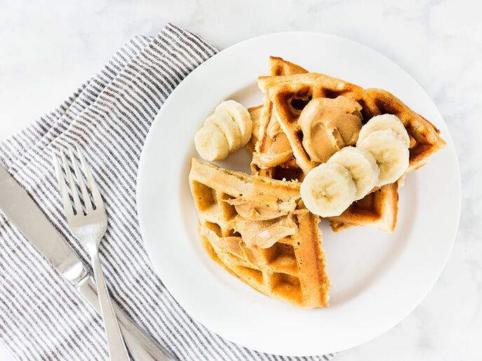 waffles on round white plate. Peanut butter and banana slices on top