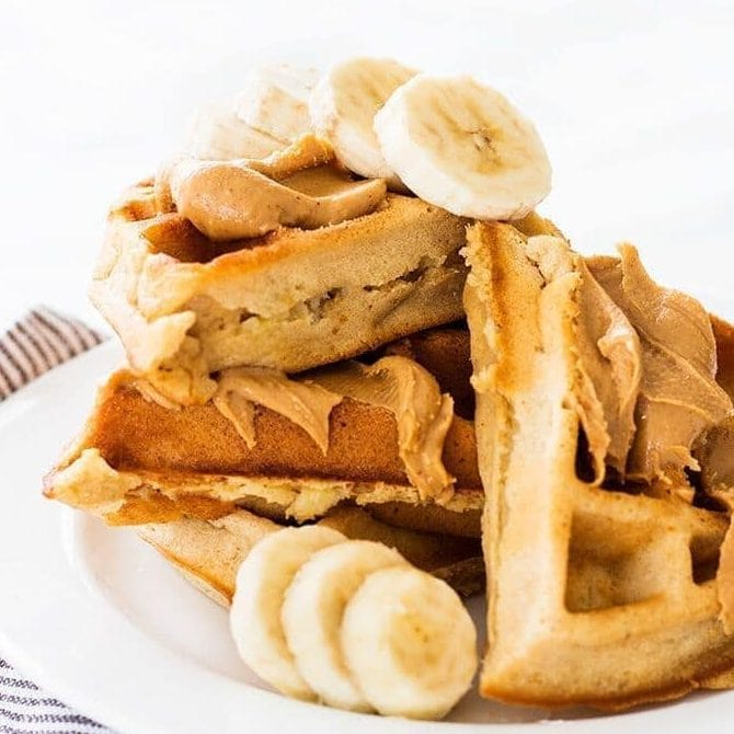stack of waffles with peanut butter spread on top and slices of banana