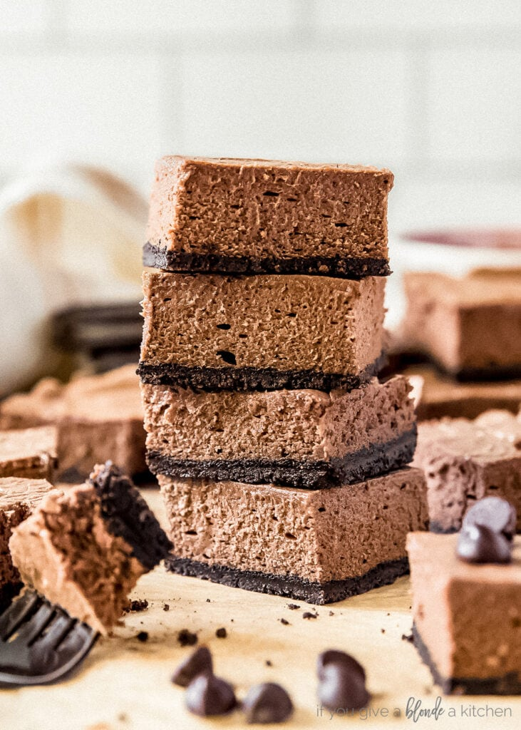 stack of four chocolate cheesecake bars with oreo crust